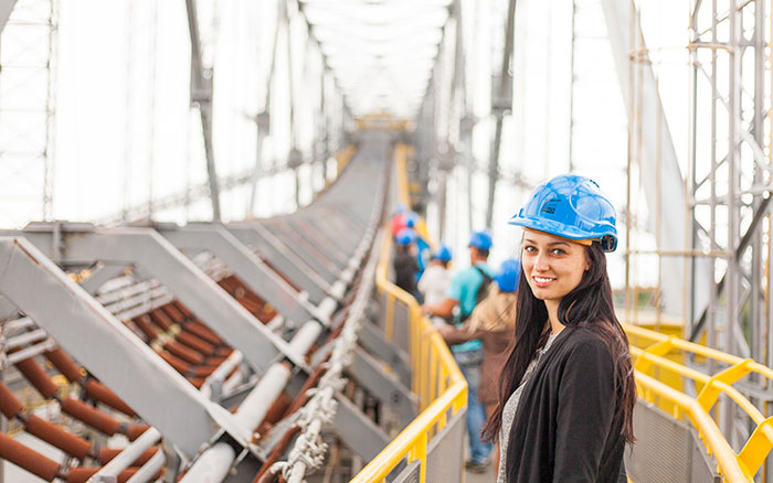 Woman wearing a hardhat on a bridge.