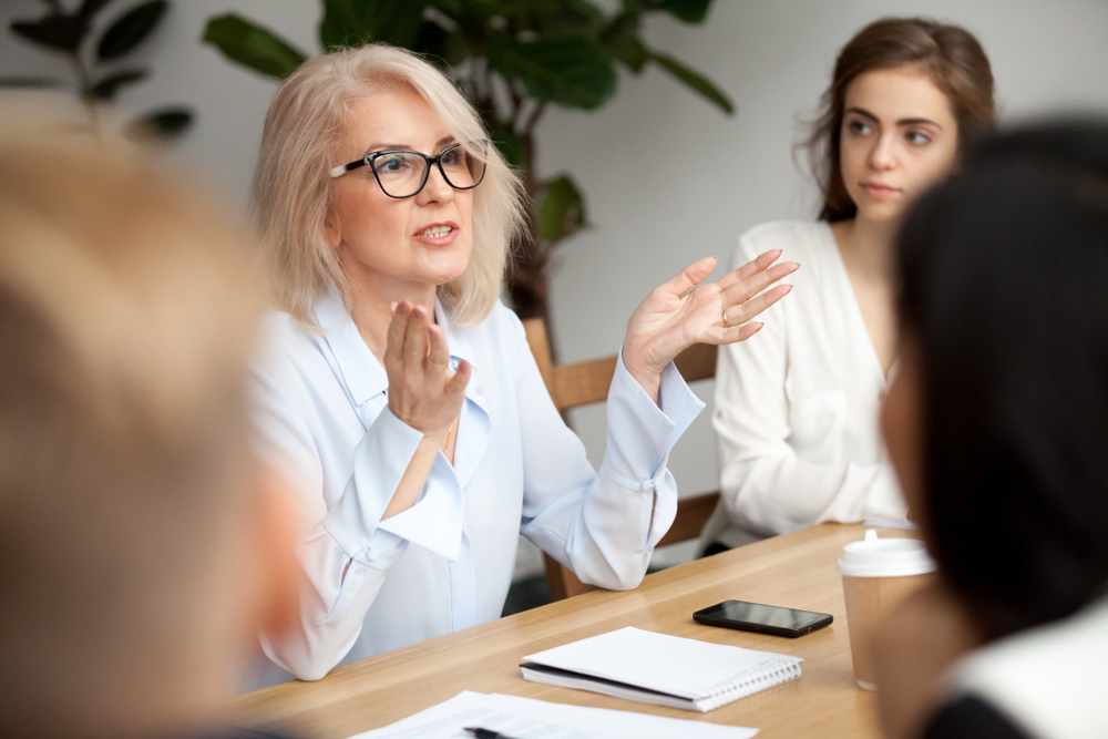 Woman sitting at a boardroom table, chatting with colleagues.