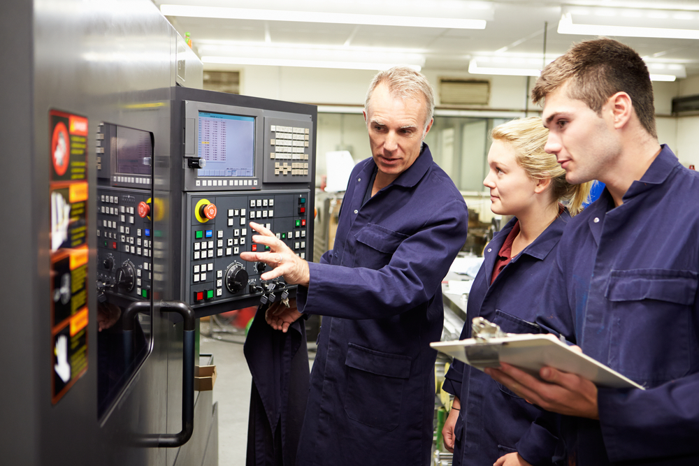 Man instructing female and male student in manufacturing plant.