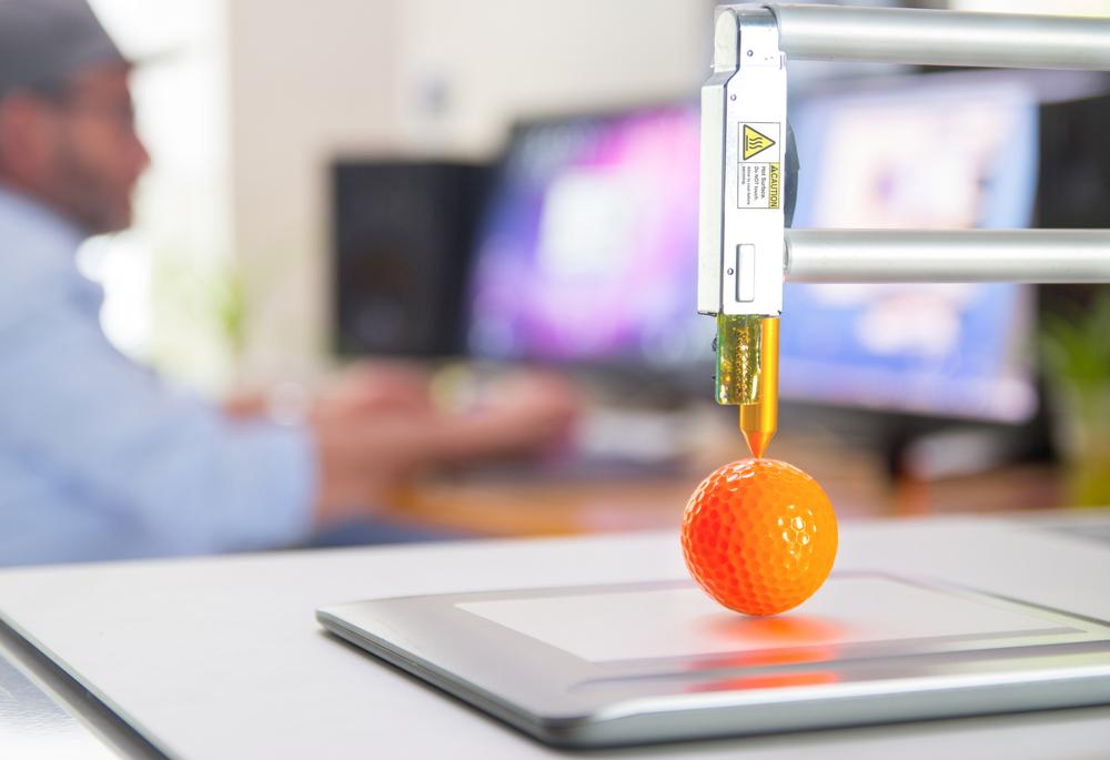 3D printer printing orange ball.