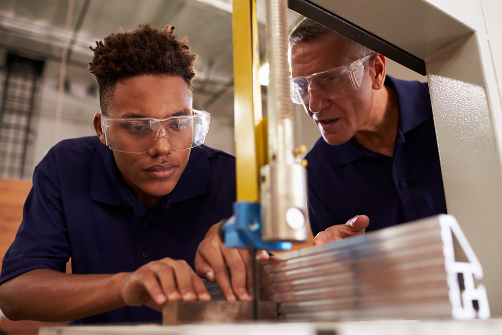 Manufacturer instructing student apprentice.
