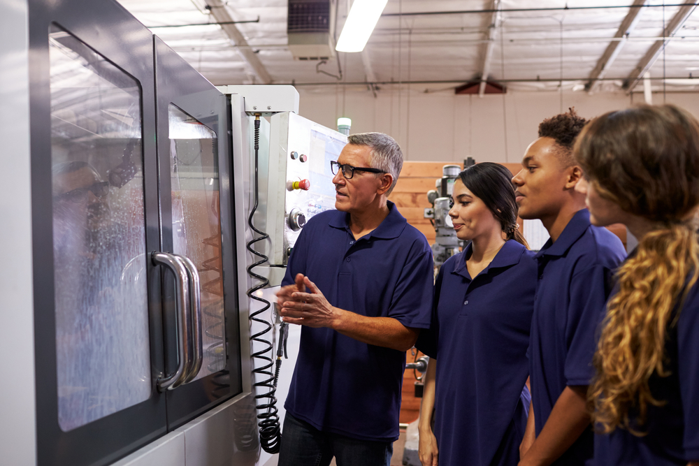 Man instructing students at manufacturing plant.