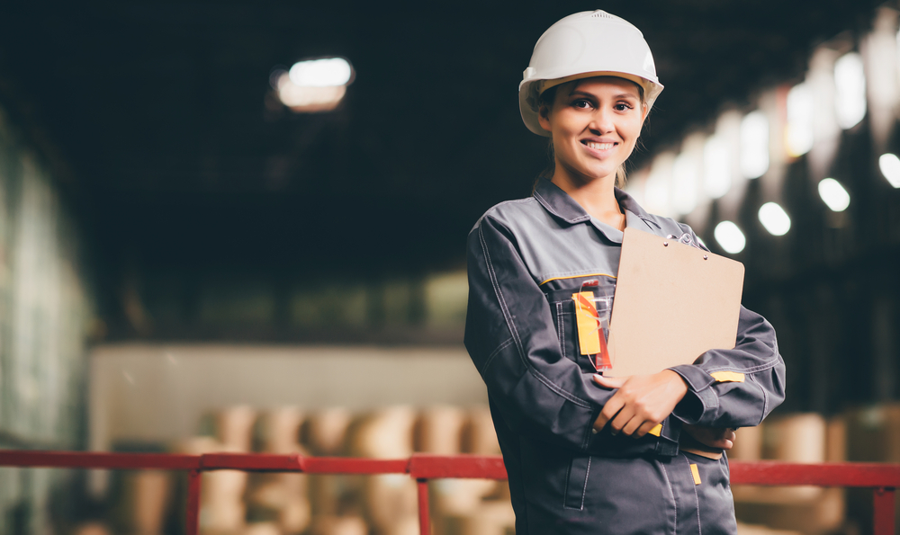 Woman wearing a hardhat in a manufacturing plant.