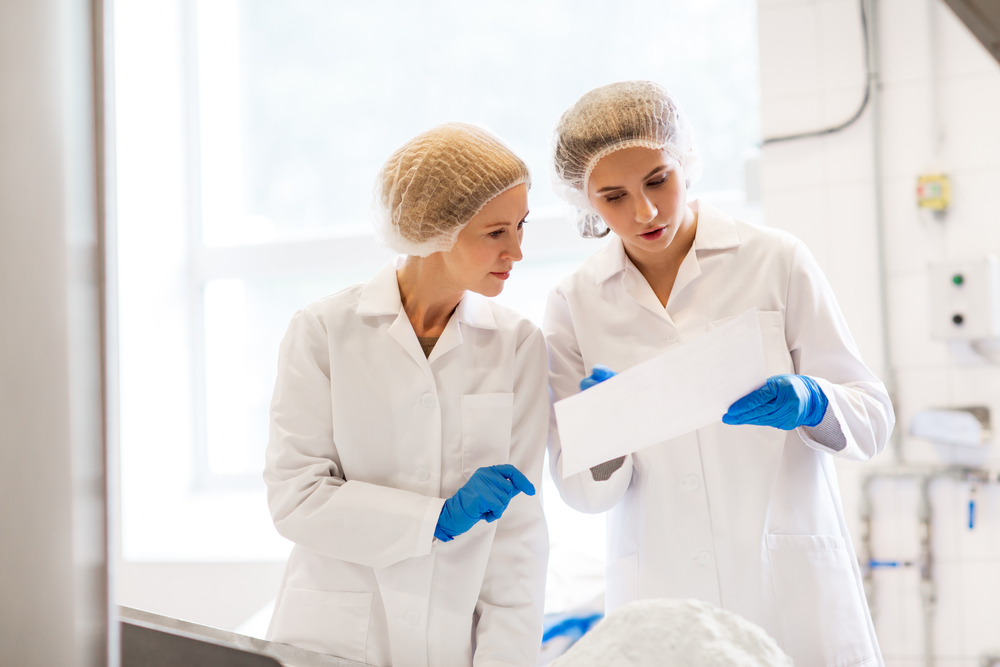 Women in manufacturing plant wearing safety gear.