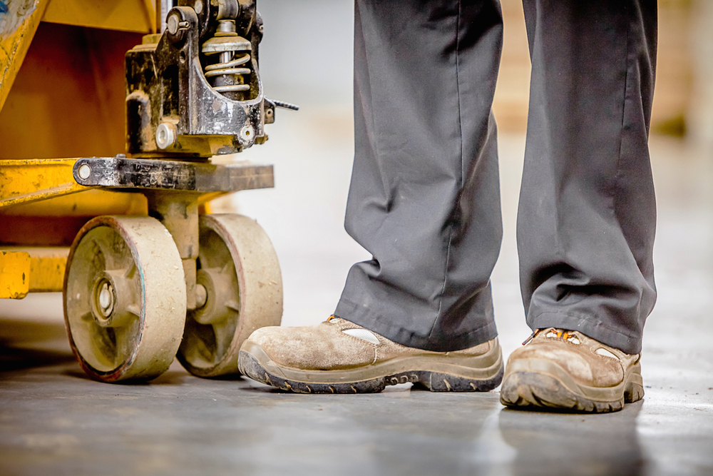 Work boots beside a manufacturing machine.