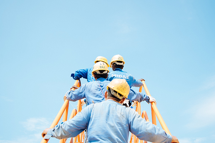 Men in hardhats climbing large construction ladder.