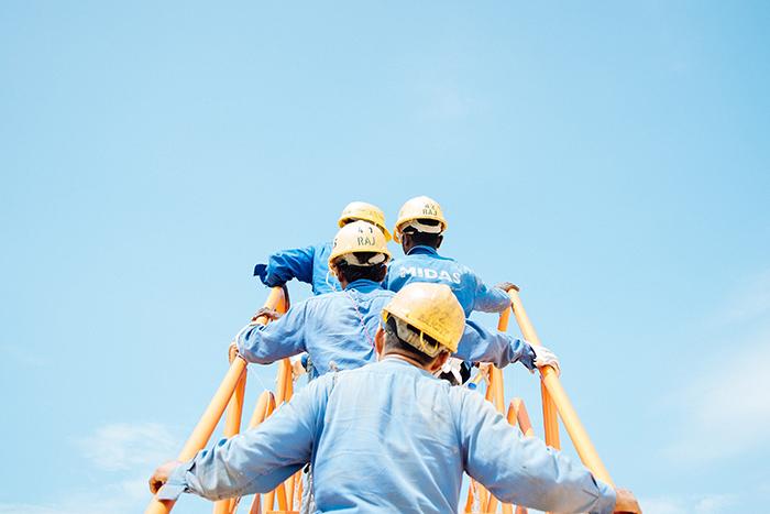 Men in hardhats climbing large construction ladder.