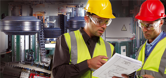 Two men in hardhats reading paper in manufacturing plant.